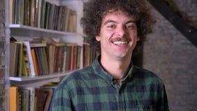 Retrato del hombre hermoso divertido que se coloca en biblioteca y que sonríe en la cámara, estantes con los libros en fondo almacen de video