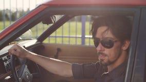 Retrato del hombre hermoso en coche potente clásico viejo en la calle, en la puesta del sol o la salida del sol almacen de video
