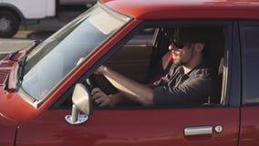 Retrato del hombre hermoso en coche potente clásico viejo en la calle, en la puesta del sol o la salida del sol almacen de metraje de vídeo