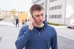 Retrato del hombre hermoso en fondo urbano que habla en el teléfono Imagen de archivo