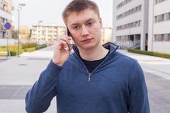 Retrato del hombre hermoso en fondo urbano que habla en el teléfono Imagen de archivo libre de regalías
