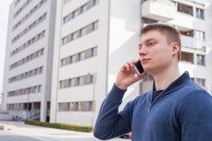Retrato del hombre hermoso en fondo urbano que habla en el teléfono Fotos de archivo libres de regalías
