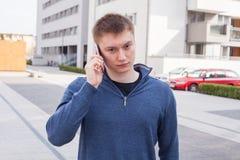 Retrato del hombre hermoso en fondo urbano que habla en el teléfono Foto de archivo