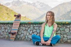 Retrato del hombre hermoso fresco, divertido con el monopatín en la montaña Foto de archivo