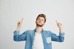 Retrato del hombre hermoso joven alegre que sonríe señalando el finger para arriba sobre el fondo blanco Foto de archivo libre de regalías