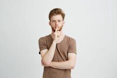 Retrato del hombre hermoso joven con la barba que mira la demostración recta de la cámara para guardar silencio sobre el fondo bl Imágenes de archivo libres de regalías