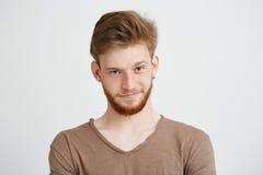 Retrato del hombre hermoso joven con la barba que mira la cámara que sonríe sobre el fondo blanco Foto de archivo libre de regalías