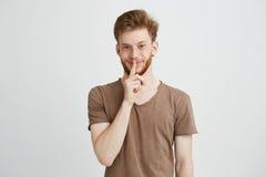 Retrato del hombre hermoso joven con la barba que mira mostrar sonriente de la cámara para guardar silencio sobre el fondo blanco Imagen de archivo