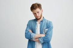 Retrato del hombre hermoso joven con los brazos cruzados que aumentan para arriba la frente que mira la cámara sobre el fondo bla Imagen de archivo libre de regalías