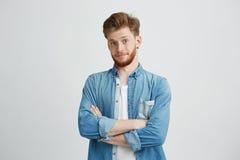 Retrato del hombre hermoso joven con los brazos cruzados que miran la cámara que sonríe sobre el fondo blanco Foto de archivo libre de regalías