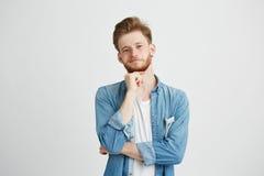 Retrato del hombre hermoso joven confiado con la barba que mira la cámara que piensa con la mano en la barbilla sobre el fondo bl Fotos de archivo libres de regalías