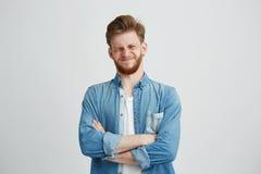 Retrato del hombre hermoso joven descontentado en camisa de la mezclilla con los brazos cruzados sobre el fondo blanco Imagenes de archivo