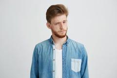 Retrato del hombre hermoso joven en la camisa de la mezclilla que aumenta para arriba la frente que mira la cámara sobre el fondo Imagen de archivo libre de regalías