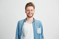 Retrato del hombre hermoso joven del inconformista con la risa sonriente de la barba mirando la cámara sobre el fondo blanco Foto de archivo