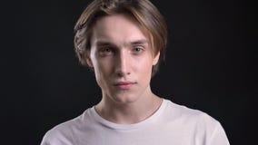 Retrato del hombre hermoso joven que mira in camera, del fondo negro, del muchacho encantador con el pelo largo y de ojos azules almacen de metraje de vídeo