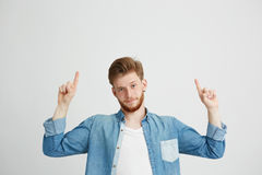 Retrato del hombre hermoso joven que mira la cámara que señala el finger para arriba sobre el fondo blanco Fotografía de archivo