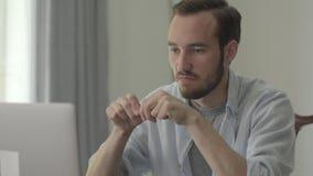 Retrato del hombre hermoso joven que rompe el lápiz con la cólera que se sienta delante de su ordenador en la oficina Problemas e almacen de video