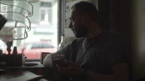 Retrato del hombre hermoso joven que se sienta en café cerca de la ventana y que usa el smartphone, practicando surf Internet almacen de video