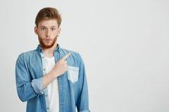 Retrato del hombre hermoso joven sorprendido que mira la cámara que señala el finger para arriba sobre el fondo blanco Imagen de archivo
