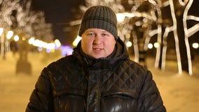 Retrato del hombre hermoso que dice sí sacudiendo la cabeza al aire libre durante noche fría del invierno almacen de metraje de vídeo