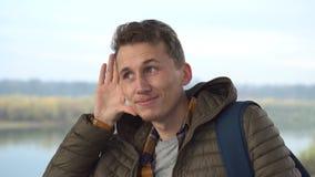 Retrato del hombre hermoso que escucha secretamente en el vuelo de prueba al aire libre metrajes