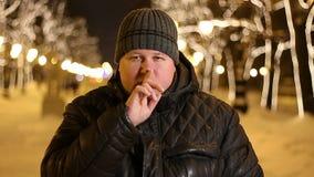 Retrato del hombre hermoso que gesticula para el silencio con el finger al aire libre durante noche fría del invierno metrajes