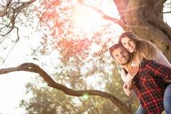 Retrato del hombre hermoso sonriente que da a cuestas a su novia en la naturaleza Imagen de archivo libre de regalías