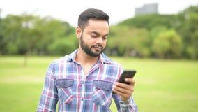 Retrato del hombre indio hermoso joven en parque usando el teléfono móvil almacen de video