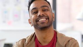 Retrato del hombre indio sonriente feliz en la oficina almacen de video
