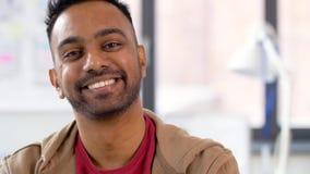 Retrato del hombre indio sonriente feliz en la oficina almacen de metraje de vídeo
