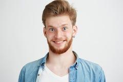 Retrato del hombre joven alegre con la barba que sonríe mirando la cámara sobre el fondo blanco Imágenes de archivo libres de regalías
