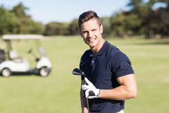Retrato del hombre joven alegre que detiene al club de golf Fotografía de archivo libre de regalías