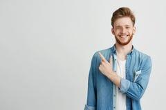 Retrato del hombre joven alegre que sonríe mirando la cámara que señala el finger para arriba sobre el fondo blanco Imagen de archivo