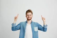 Retrato del hombre joven alegre que sonríe mirando la cámara que señala el finger para arriba sobre el fondo blanco Foto de archivo libre de regalías