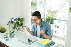 Retrato del hombre joven asiático emocionado que trabaja en el ordenador portátil a Imagenes de archivo