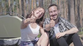 Retrato del hombre joven barbudo hermoso y de la mujer feliz bastante joven que se incorporan cerca de los pulgares de la demostr metrajes