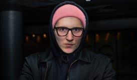 Retrato del hombre joven casual de moda que se coloca en fondo abstracto oscuro Imagen de archivo
