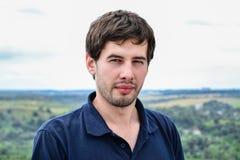 Retrato del hombre joven casual serio contra paisaje Imagen de archivo