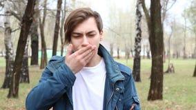 Retrato del hombre joven caucásico hermoso que es estornudos en el parque almacen de metraje de vídeo