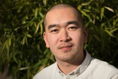 Retrato del hombre joven chino sonriente contra el fondo de bambú Imágenes de archivo libres de regalías