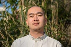 Retrato del hombre joven chino sonriente contra fondo de lámina Fotografía de archivo libre de regalías