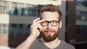 Retrato del hombre joven con la barba que se coloca delante del sol y del centelleo El hombre de negocios atractivo saca los vidr almacen de video