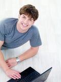 Retrato del hombre joven con la computadora portátil del eith de la sonrisa Fotos de archivo