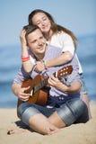 Retrato del hombre joven con la guitarra y la mujer en una playa Fotografía de archivo