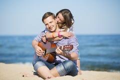 Retrato del hombre joven con la guitarra y la mujer en una playa Imagenes de archivo