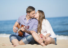 Retrato del hombre joven con la guitarra y la mujer en una playa Fotografía de archivo libre de regalías