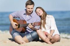 Retrato del hombre joven con la guitarra y la mujer en una playa Foto de archivo