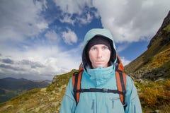 Retrato del hombre joven con la mochila en el fondo de un paisaje de la montaña y de un cielo azul con las nubes blancas Montaña Fotografía de archivo libre de regalías