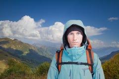 Retrato del hombre joven con la mochila en el fondo de un paisaje de la montaña y de un cielo azul con las nubes blancas Montaña Imagen de archivo libre de regalías