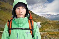 Retrato del hombre joven con la mochila en el fondo de un paisaje de la montaña y de un cielo azul con las nubes blancas Montaña Foto de archivo libre de regalías